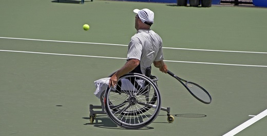 Wheelchair bound athlete playing tennis