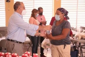Director Inabie entrega raciones de leche a una madre